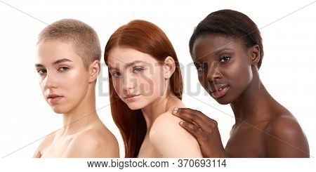 Three Gorgeous Multicultural Young Women Embracing And Looking At Camera While Standing Close To Eac