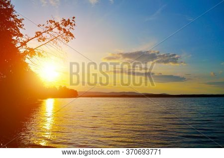 Summer landscape - summer sunset over the Irtyash lake in Southern Urals, Russia, summer sunset water landscape, colorful sunset summer view. Summer scene, sunset summer background. Summer nature at sunset