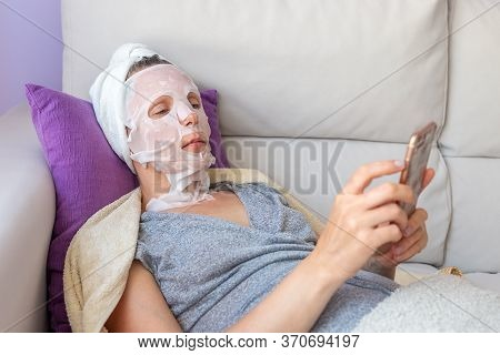 Woman In Cosmetic Mask With Phone Lies On Sofa