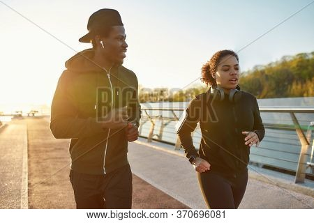 Starting New Day From Morning Jog. Young African Couple In Sportswear Jogging Together On The Bridge