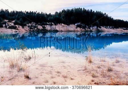 Summer landscape of summer kaolin quarry locally named Bali. Kyshtym, South Ural, Russia. Colorful summer view of summer cloudy nature. Summer water background, summer forest at the bank of the summer blue quarry