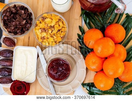 Breakfast On The Table. Corn Flakes, Milk, Butter, Strawberry Jam, Bread, Coffee, Tea And Fruit On A