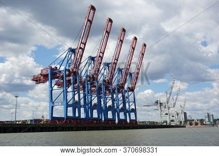 Hamburg, Germany - 05/30/2020: Picture Of The Blue Cranes In The Harbour Of Hamburg