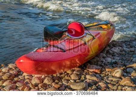 whitewater kayak with a helmet and paddle on a river shore, Poudre River in Fort Collins, Colorado