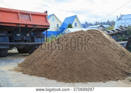 Pile Of Sand On Ground In Foreground And Dump Truck In Background On Construction Site