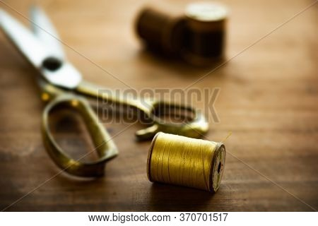 Old bobbin with gold thread with gold scissors in backgound.