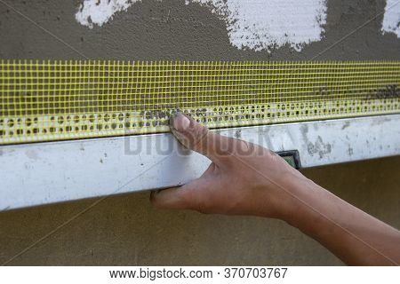 Mounting Corner Is Perforated On The Facade, Builders Hand Glues On The Facade Of The Corner With A