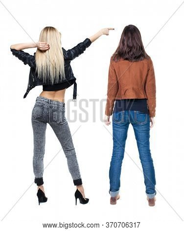 Back view of two pointing girl in winter jacket. Rear view people collection. backside view of person. beautiful woman friends showing gesture. Rear view. Isolated over white background.