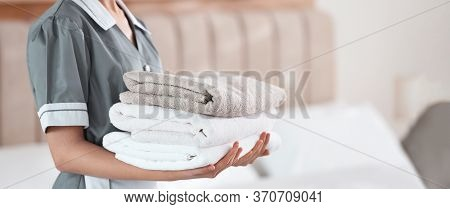 Young Chambermaid Holding Stack Of Fresh Towels In Bedroom, Closeup. Banner Design