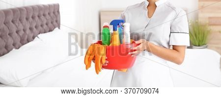 Young Chambermaid Holding Cleaning Supplies In Bedroom, Closeup View With Space For Text. Banner Des
