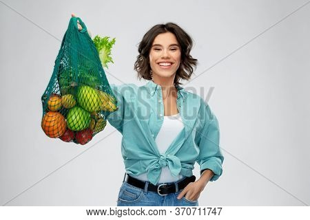 sustainability, food shopping and eco friendly concept - happy smiling woman in turquoise shirt and jeans holding reusable net bag with fruits and vegetables on grey background