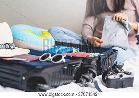 Preparing Suitcase For Summer Vacation Trip. Young Woman Checking Accessories And Stuff In Luggage O