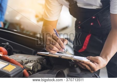Auto Check Up And Car Service Shop Concept. Mechanic Writing Job Checklist To Clipboard To Estimate