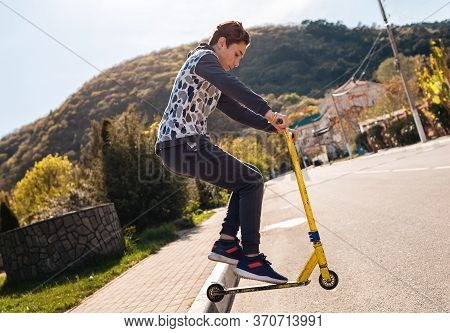 A Teenager Performs A Trick On A Scooter, Jumping Off The Sidewalk On It. In The Background-an Empty