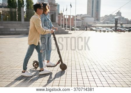 Full-length Portrait Of Asian Boy Showing His Female Friend How To Ride E-scooter. Millennial Guys U