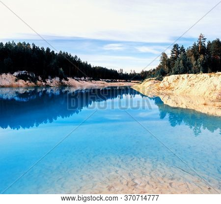Summer water landscape of kaolin quarry locally named Bali. Kyshtym, South Ural, Russia. Colorful summer view, summer water landscape, summer water scene. Summer water forest background