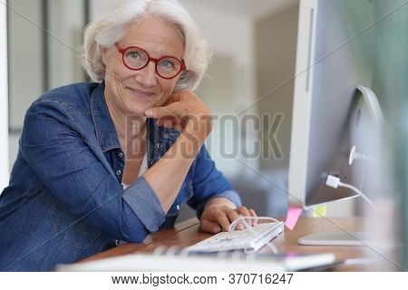 Senior woman working on desktop computer at home