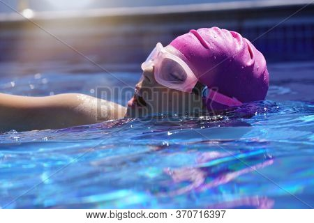 Young girl training in outdoor swimming-pool