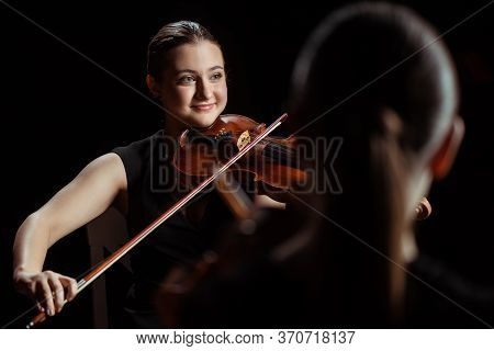 Professional Musicians Playing Classical Music On Violins On Dark Stage