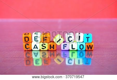 Alphabet Beads On Conceptual Deficit Cash Flow On Red Surface.