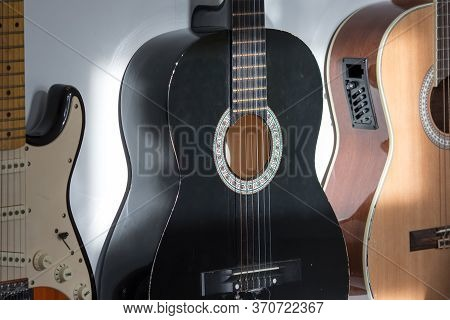 Acoustic And Electric Guitars Hanging On A Music Room Wall. Assorted Guitars Including A Black Class