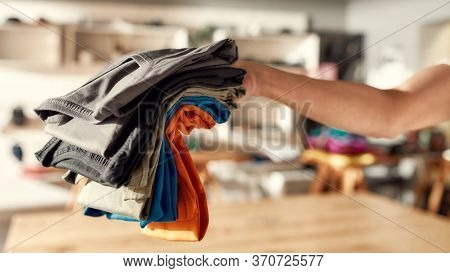 Cropped Shot Of Hand Of Woman Holding Stack Of Colorful T Shirts While Standing In The Store. Clothe