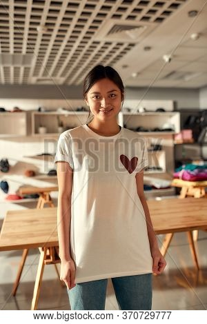 Young Woman Smiling At Camera, While Trying On Printed T Shirt, Standing In The Store. Clothes At Cu