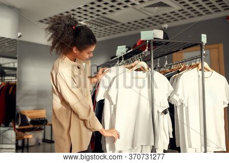 Young Woman Looking At Already Made Items In The Store. Choosing Clothes At Custom T-shirt, Clothing