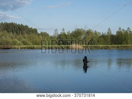 Fly Fisherman Angler Standing In Calm Water Of Forest Lake, Fish Pond Kunraticky Rybnik With Birch A
