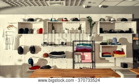 Custom Apparel, Clothes Neatly Arranged Or Folded On Shelves. Stack Of Colorful Clothing And Basebal
