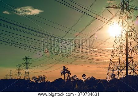 Electric Power Line Plant Station Tower Pole In The Field On Sunset Background. Abstract Energy Powe