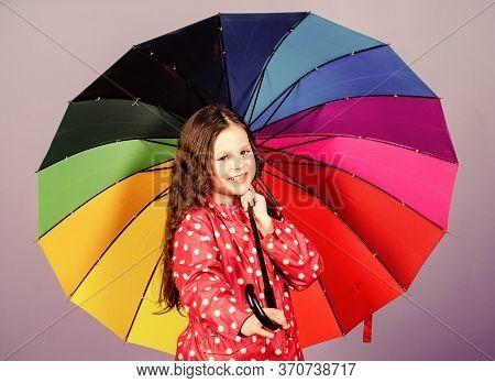 Kid Girl Happy Hold Colorful Rainbow Umbrella. Rainy Weather With Proper Garments. Bright Umbrella.