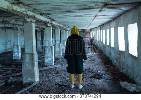 A Girl In A Gloomy Abandoned Building In A Black Cloak. Young Woman In An Industrial Abandoned Facto