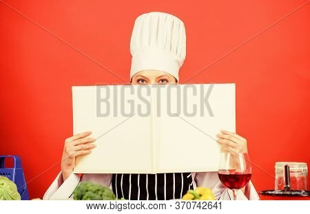 Cook Looking For Cooking Recipe In Cookbook. Woman Reading Cook Book In Kitchen. Girl Cook At Kitche
