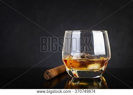 Glass Of Whiskey And Cigar On Dark Background.