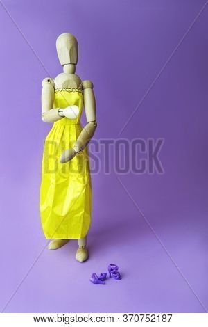 Concept Of Gender Dysphoria And Transgenders. Gestalta Wearing A Yellow Dress, Woman Shoes On Purple