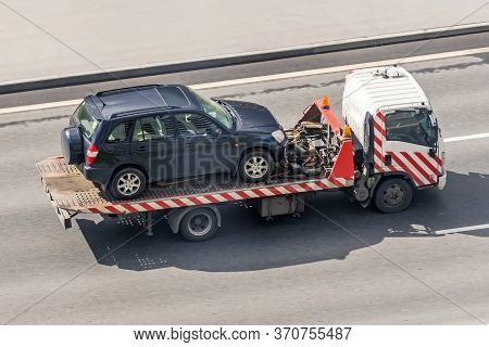 Tow Truck Carries An Evacuated Car On A Highway, Aerial View