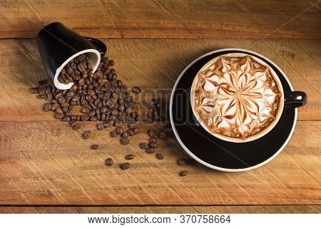 Top View Of Hot Coffee Latte (or Cappuccino) In A Black Cup With Latte Art And Roasted Coffee Beans