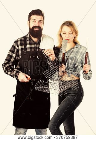 Couple In Love Hold Cooking Utensils For Barbecue. Tools For Roasting Meat Outdoors. Picnic And Barb