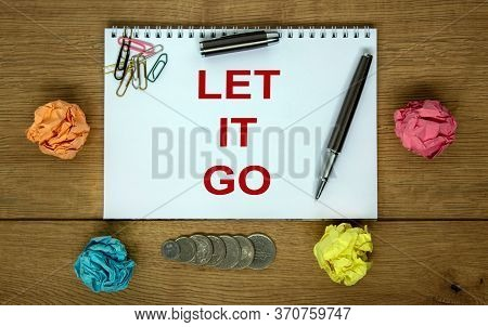 White Note With Inscription 'let It Go' On Beautiful Wooden Table, Colored Paper, Metalic Pen. Busin