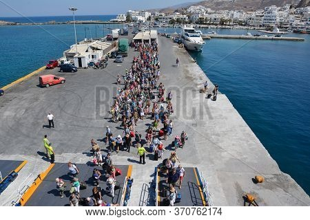 Naxos, Greece - September 17, 2016: Passengers And Cars Embark On A Ship At The Port Of Naxos In Gre