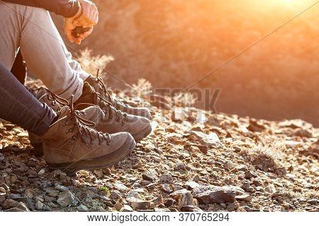 Tourist In Trekking Hiking Boots Walking On Mountain On Sunset