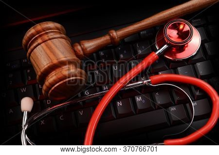 An Overhead View Of A Legal Wood Gavel And Doctors Stethoscope Resting On Top Of A Black Keypad And