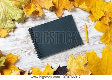 Spiral Black Notepad And Pen Lies On Vintage Wooden Desk With Bright Autumn Foliage. Business And Ed