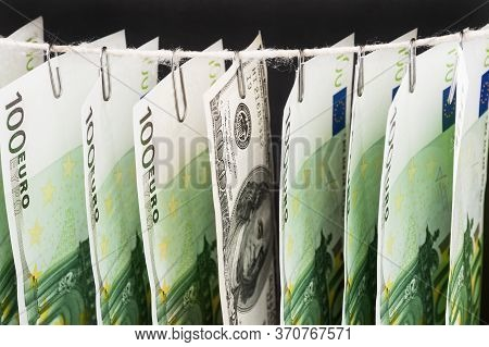 Parts Of Hundred Euro Bills And One Hundred Dollar Bill Between Them Is Hanging On Clerical Clips On