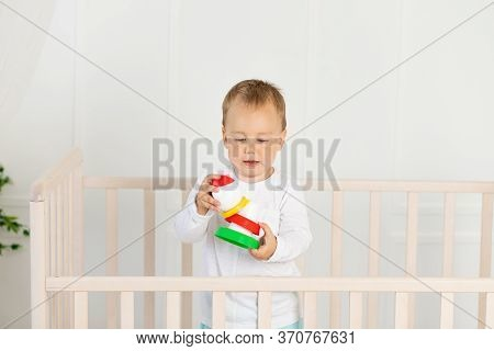 Four Months Old Little Boy Playing In Baby Bed. Toys Are Officially Property Released