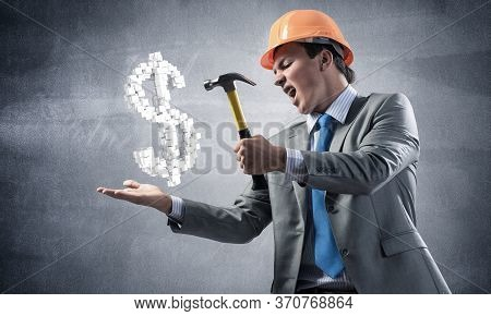 Furious Businessman Going To Crash With Hammer Dollar Symbol. Young Handsome Man In Business Suit An