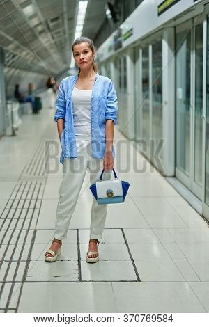Woman Inside Metro Subway Waiting On The Platform Of A Railway Station For Train To Arrive.