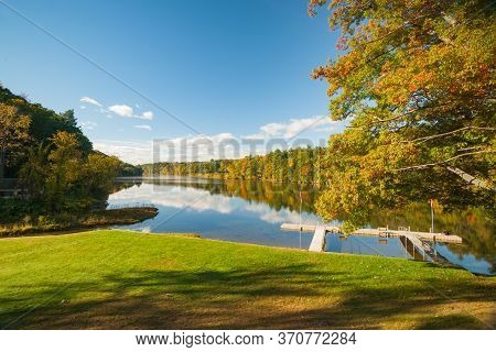 Beautiful Connecticut River Lined By Autumn Foliage Forest With Jetty And Oak Tree In Foreground Nea