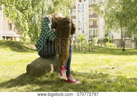 Long-haired Girl In Red Sneakers, Jeans And A Checkered Green Shirt Sits On A Stone In A Summer Park